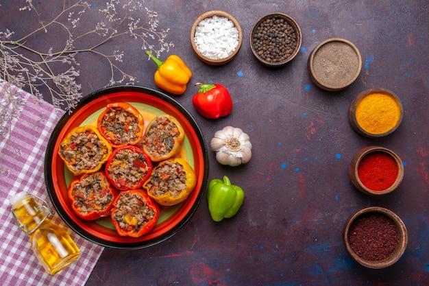 Vista dall'alto peperoni cotti con diversi condimenti sul pavimento grigio scuro cibo dolma verdure farina di manzo