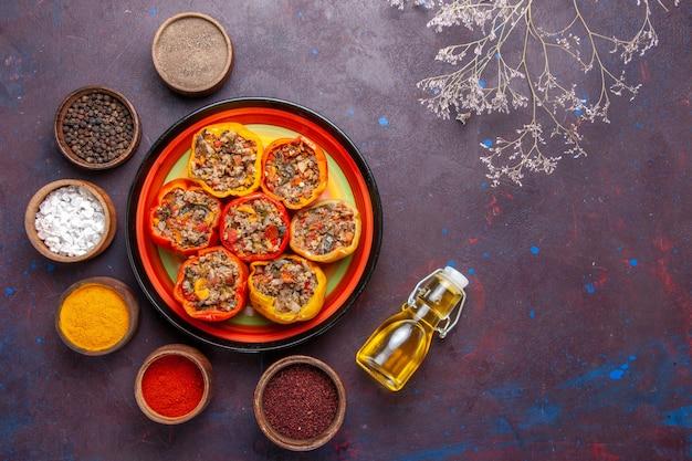 Vista dall'alto peperoni cotti con diversi condimenti sulla superficie grigio scuro cibo dolma farina vegetale di manzo