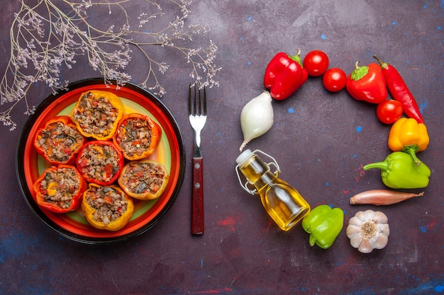 Vista dall'alto peperoni cotti con diversi condimenti sulla scrivania grigia manzo dolma cibo verdure carne