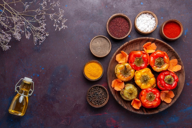Top view cooked bell-peppers with different seasonings on grey desk meal vegetables meat dolma food