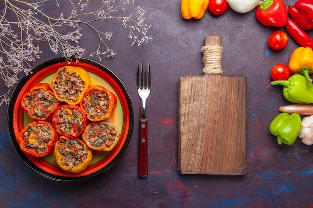 Vista dall'alto peperoni cotti con diversi condimenti sul pavimento grigio cibo manzo dolma carne di verdure