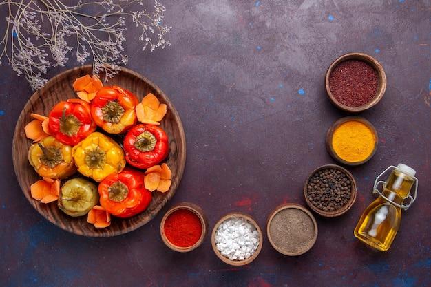 Vista dall'alto peperoni cotti con diversi condimenti su farina di superficie grigia verdure carne dolma cibo