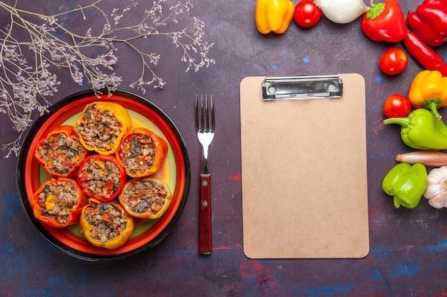 灰色の表面にさまざまな調味料を加えた上面図調理済みピーマン食品牛肉ドルマ野菜肉