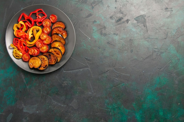 Top view cooked bell-peppers with eggplants on dark-green surface