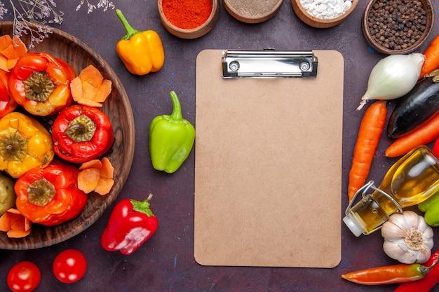 灰色の机の上の新鮮な野菜と調味料を使った上面図調理済みピーマンドルマ野菜牛肉