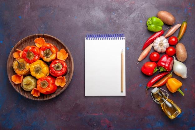 暗い机の上に新鮮な野菜を添えた上面図調理済みピーマン食事野菜肉ドルマ食品 無料写真