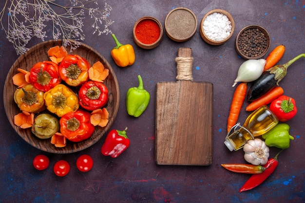 Top view cooked bell-peppers with fresh vegetables and seasonings on grey surface meal dolma vegetables beef meat