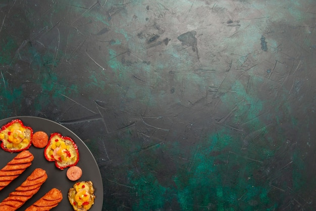 Top view cooked bell-peppers with fried sausages inside plate on dark green surface