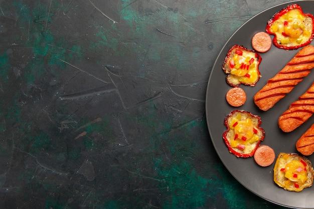 Вид сверху приготовленный болгарский перец с жареными сосисками внутри тарелки на темно-зеленом столе