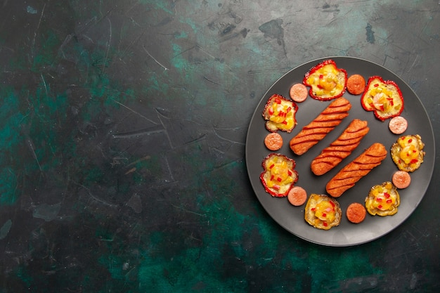Вид сверху приготовленный болгарский перец с жареными сосисками внутри тарелки на темно-зеленой поверхности