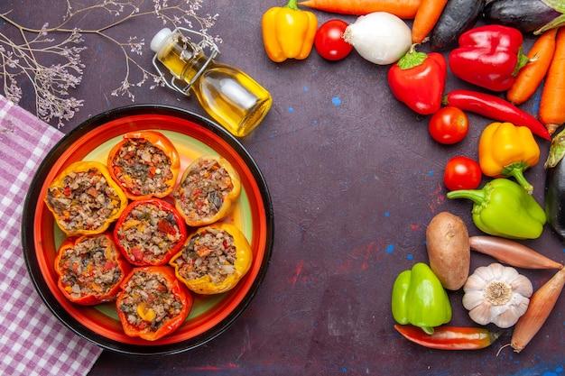 ひき肉と新鮮な野菜を暗い表面に載せた上面図調理済みピーマン食事野菜食品肉ドルマ