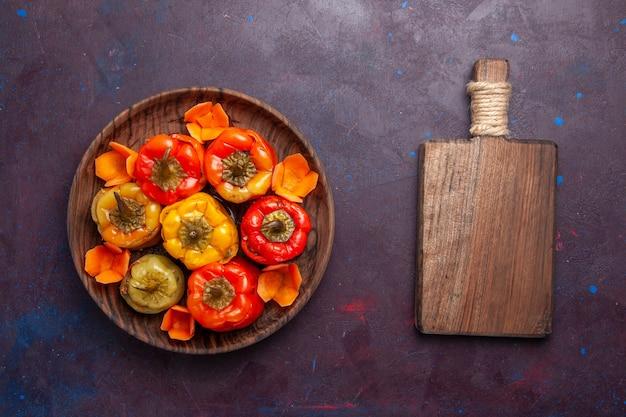 Vista dall'alto peperoni cotti con carne macinata all'interno sulla superficie grigia pasto carne cibo cucina vegetale