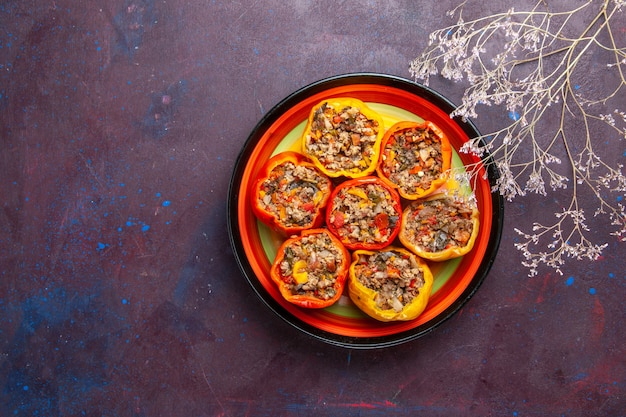 Vista dall'alto peperoni cotti con carne macinata all'interno della piastra sulla superficie grigio scuro cibo dolma farina di verdure manzo