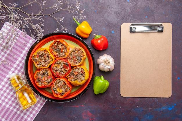 Vista dall'alto peperoni cotti con carne macinata e blocco note su una superficie scura cibo verdure carne dolma dolma