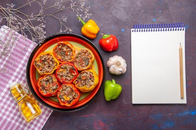 Vista dall'alto peperoni cotti con carne macinata e olio su una superficie scura cibo vegetale dolma di carne