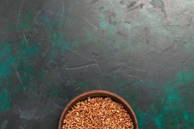 Вид сверху приготовленной гречневой вкусной еды внутри коричневой тарелки на темно-зеленой поверхности