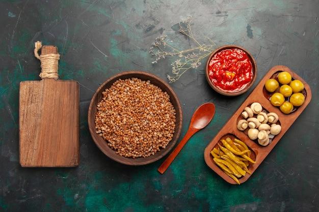 Vista dall'alto di grano saraceno cotto con salsa di pomodoro sulla superficie verde scuro