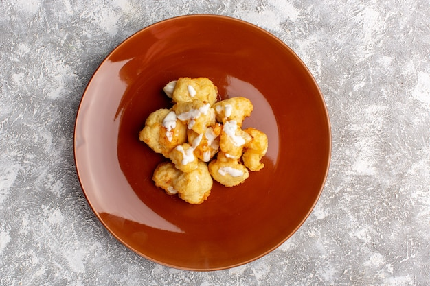 Top view of cooked cauliflower inside brown plate on light surface