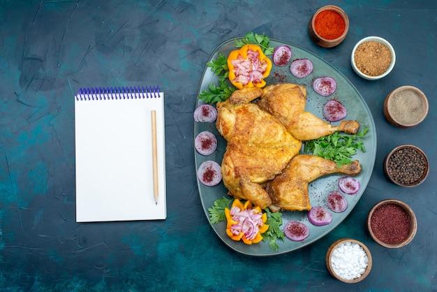 紺色の机の上のプレートの内側に玉ねぎと緑が入った上面図調理済みチキンチキンミートベイクオーブンディナー