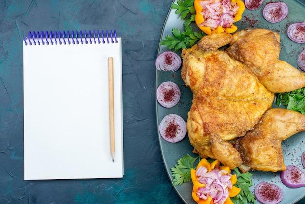 Vista dall'alto pollo cotto con cipolle e verdure all'interno della piastra con blocco note sulla scrivania blu scuro carne di pollo cuocere la cena al forno