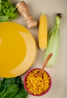 Top view of cooked corn seeds with corn cobs spinach and lettuce with empty plate on white surface