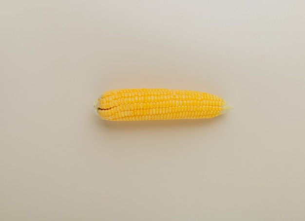 Top view of cooked corn on white surface with copy space