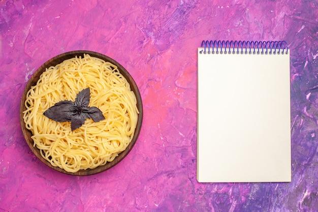 ピンクの床のパスタ生地の食事皿のプレートの内側の上面調理されたおいしいスパゲッティ