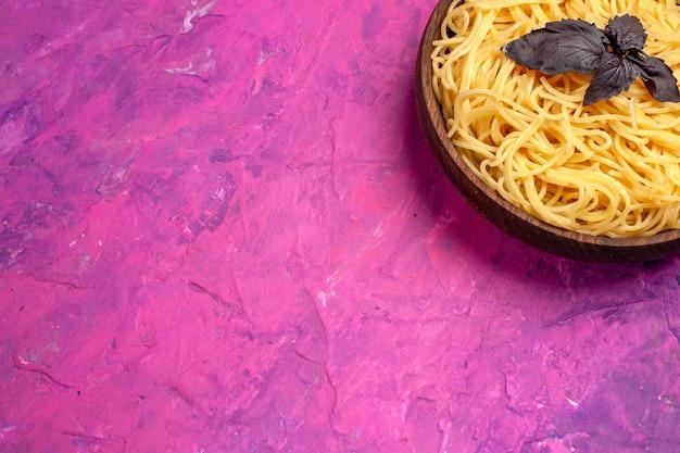 Вид сверху приготовленные вкусные спагетти внутри тарелки на розовой столовой пасте из теста