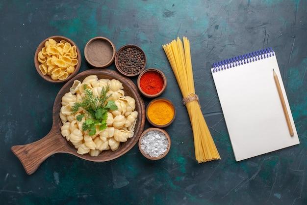 Vista dall'alto pasta cotta con diversi condimenti su pasta di farina di farina di pavimento scuro italiano