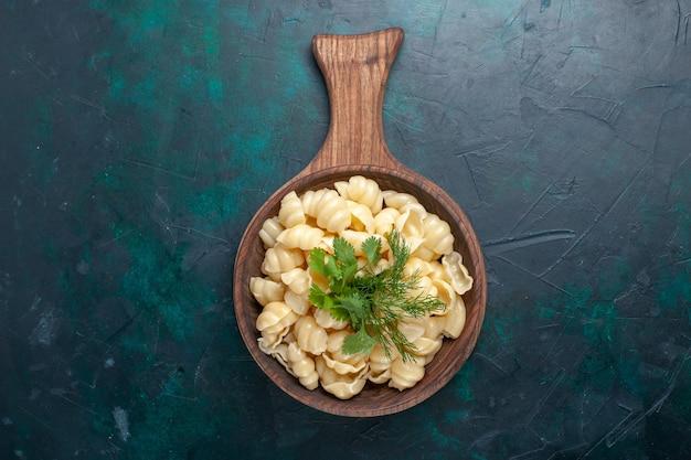 Vista dall'alto pasta cotta con verdure all'interno del piatto sulla superficie scura