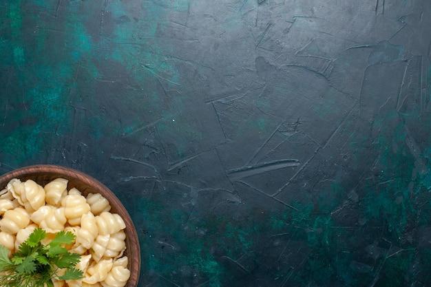 暗い表面のプレートの内側に緑のある上面図調理済み生地パスタ