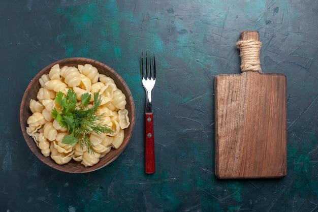 어두운 책상에 접시 안에 채소와 함께 상위 뷰 요리 반죽 파스타