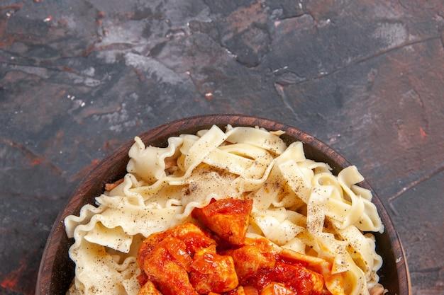上面図暗い表面のパスタ生地の暗い皿にチキンとソースで調理された生地