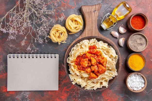 어두운 바닥 반죽 어두운 파스타 접시에 닭고기와 조미료와 함께 조리 된 반죽을 상위 뷰 무료 사진