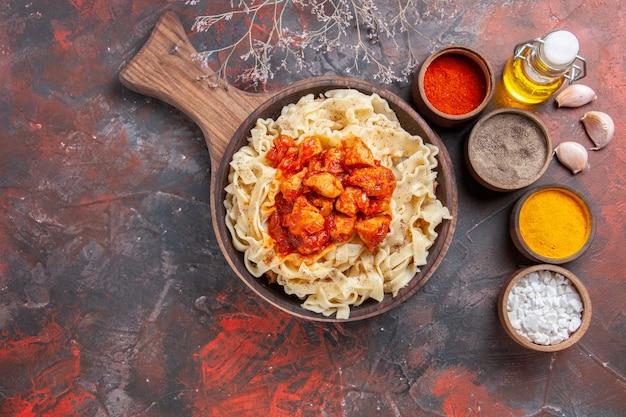 暗い表面のパスタ生地の暗い皿に鶏肉と調味料で調理された生地の上面図