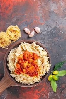 Vista dall'alto pasta cotta con pollo e salsa sul piatto di pasta scura superficie scura