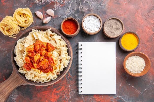 Vista dall'alto pasta cotta con pollo e salsa su un piatto di pasta scura di superficie scura