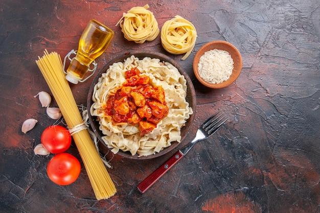 Vista dall'alto di pasta cotta con riso e carne in salsa su un piatto di pasta scura superficie scura
