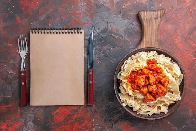 Top view cooked dough with sauce meat on dark floor dough dark pasta dish