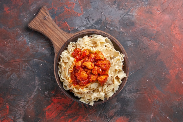 Vista dall'alto di pasta cotta con salsa di carne su pasta di superficie scura pasta scura