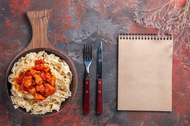 Vista dall'alto di pasta cotta con salsa di carne su un piatto scuro pasta di superficie scura pasta