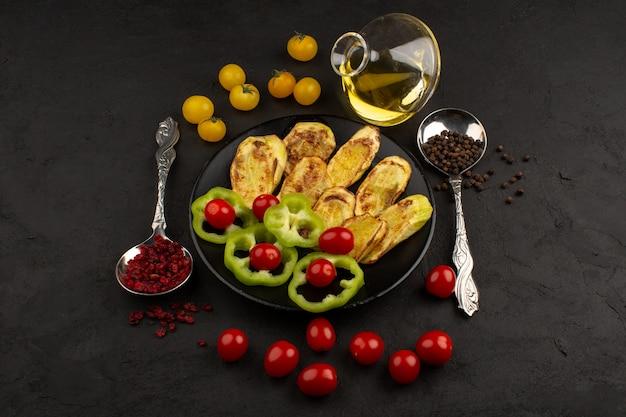 Вид сверху приготовленный баклажан вместе со свежими овощами внутри черной тарелке на темном фоне