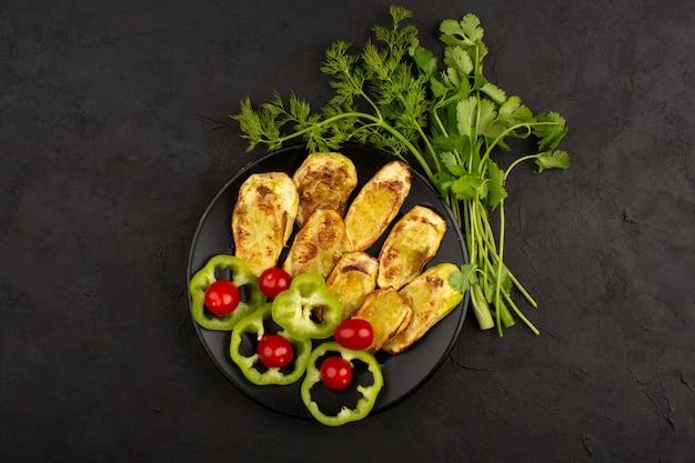 Вид сверху приготовленный баклажан внутри черной пластины вместе с нарезанным зеленым перцем и красными помидорами черри на темноте