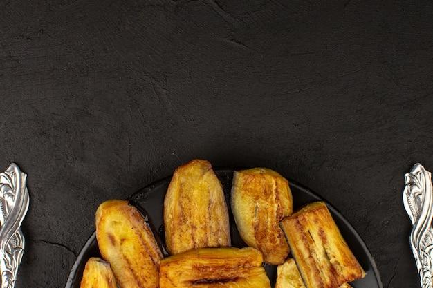 Вид сверху приготовленный баклажан внутри черной тарелке на темном фоне