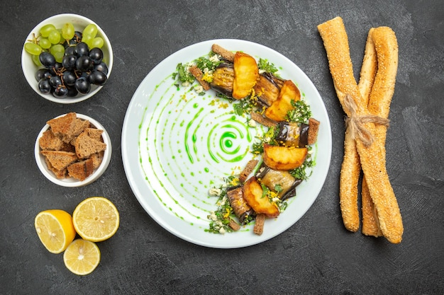 暗い背景の皿の夕食の食事の果物の料理のブドウのパンとレモンのスライスと上面図調理されたナスのロール