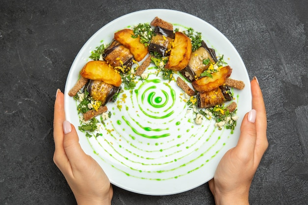 Top view cooked eggplant rolls with potatoes inside plate on dark background dish meal dinner potato