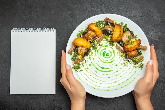 Vista dall'alto involtini di melanzane cotti con patate all'interno del piatto sullo sfondo scuro piatto cena patate