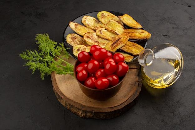 暗い床にナスと赤いトマトとオリーブオイルのトップビュー