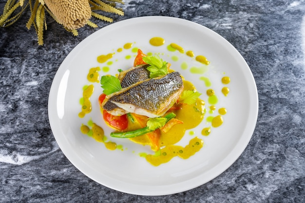 Вид сверху приготовленное филе сибаса с зеленым соусом и овощами на мраморном столе. гриль сибас ресторан стиль еды. скопируйте пространство для дизайна. картинка для меню, рецепт или постер. морепродукты