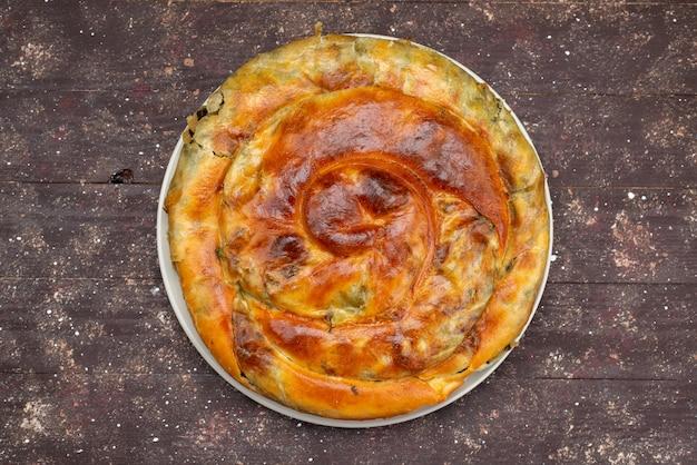 茶色の木製デスク食品食事ペストリーグリーンのラウンドプレート内の平面図調理グリーンペストリー